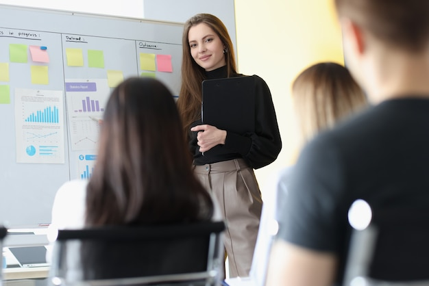 Бизнес-тренер женщина, стоя у доски перед слушателями студентов