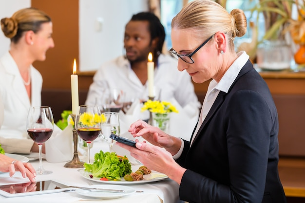 Woman on business lunch checking mails on phone