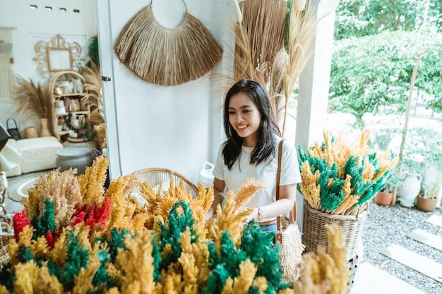 Владелец бизнеса женщина в ремесленной мастерской с цветочными поделками на корзине