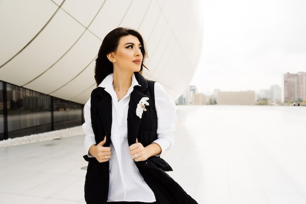 Woman in business suit posing against the background of large windows