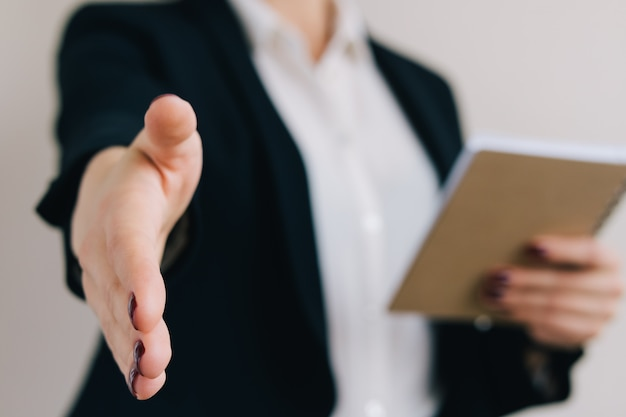 Woman in a business suit with a notebook holds out her hand for a handshake closeup