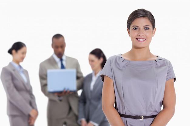 ラップトップを見て、バックグラウンドで女性のビジネスチーム