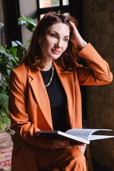 Woman in a business terracotta jacket sits with a book in her hands and straightens her hair