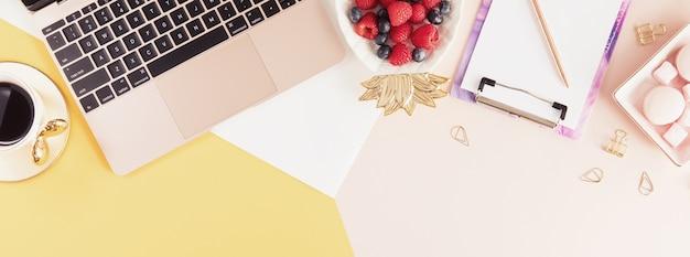 밝은 노란색과 분홍색 배경에 노트북, 꽃, 녹색 야자수 잎이 있는 여성 비즈니스 직장. 여름 시간에 여성의 작업 공간의 상위 뷰. 플랫 레이