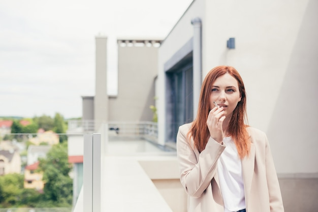 여성 사업가는 발코니에서 담배를 피우고, 사무실 센터 스트레스와 직장 피로