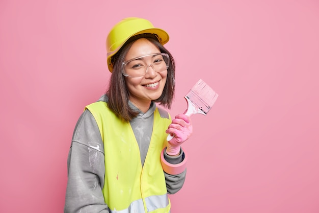 Woman busy with refurbishment and renovation wears safety clothes holds painting brush