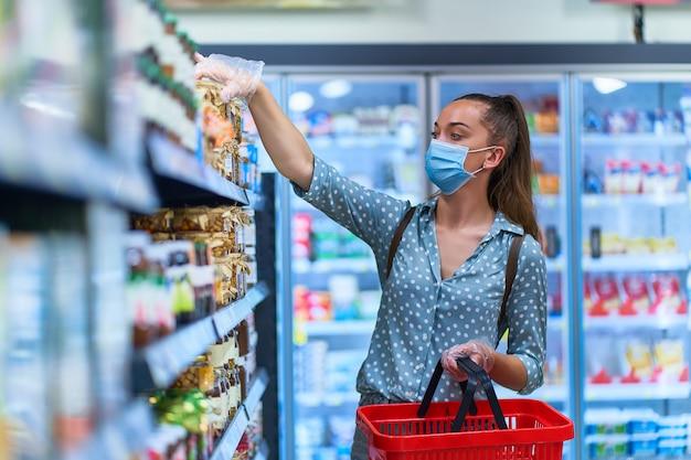 防護マスクと買い物かご付きの透明な手袋の女性バイヤーは、食料品店で食品を選択します