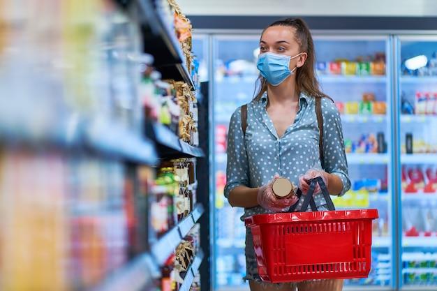 買い物かごの防護マスクの女性バイヤーは、食料品店の棚にある食品を選ぶ