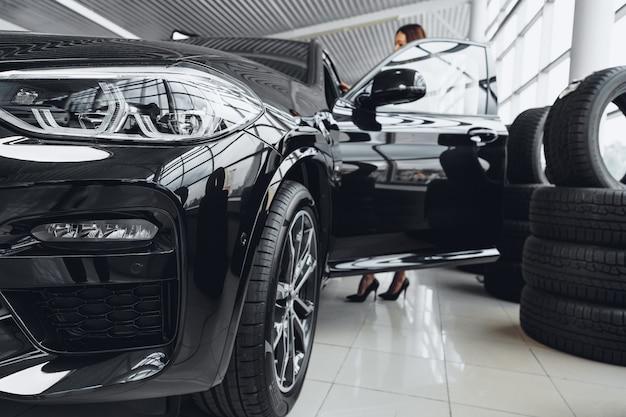女性のバイヤーは車のショールームで黒い車に座る