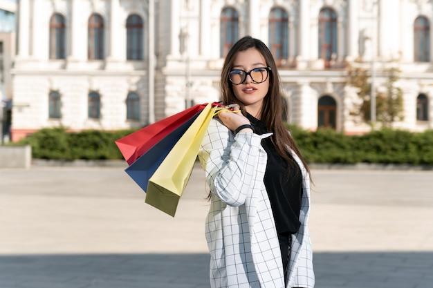 아름 다운 건물 배경에 여러 쇼핑 가방 여성 구매자.