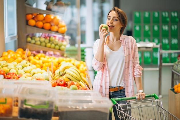 Женщина покупает в продуктовом магазине