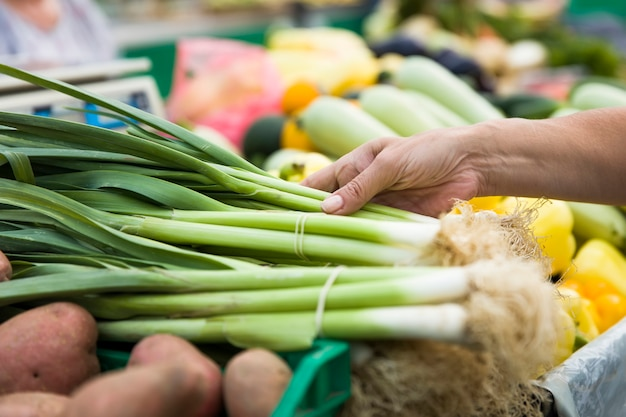 Woman buying bunches of spring onions on stall at the market