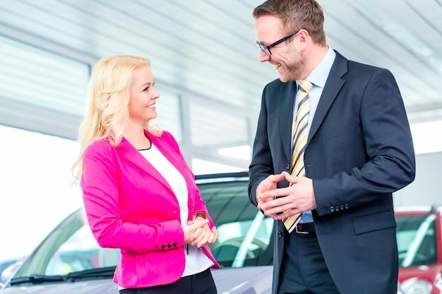 ディーラーで車を購入し、セールスマンに相談する女性