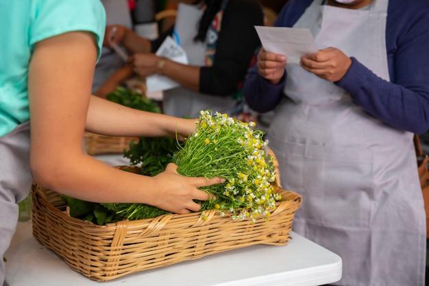 Женщина, покупая ромашки на местном рынке