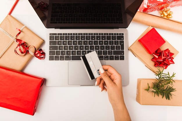 Woman buying christmas presents online with gifts on table