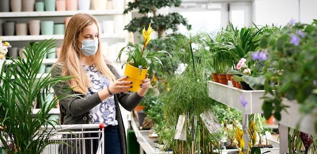 花を買う女性ショッピングカートガーデンセンター。バナー。