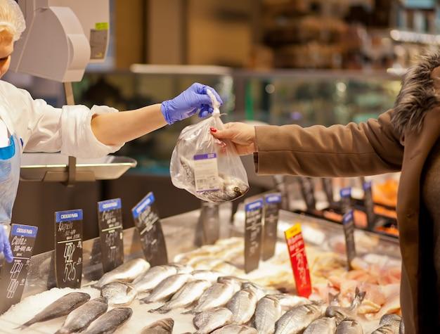 Woman buying fresh fish seafood in supermarket retail store