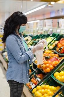 Женщина покупает фрукты в супермаркете с зеленой маской. открытие полиэтиленового пакета