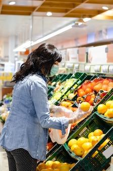 Женщина покупает фрукты в супермаркете с зеленой маской