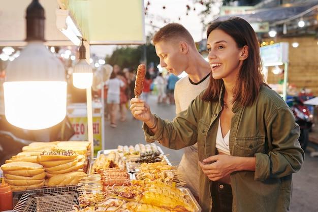 Женщина покупает шашлык из свинины на гриле