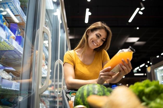 スーパーマーケットで食料品を買う女性