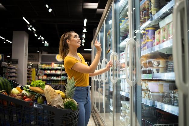 Женщина покупает продукты в супермаркете