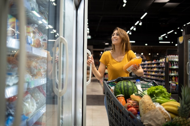 Woman buying groceries in supermarket.