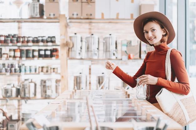 플라스틱 없는 식료품점 제로 웨이스트 샵에서 현지 제품을 사는 여성
