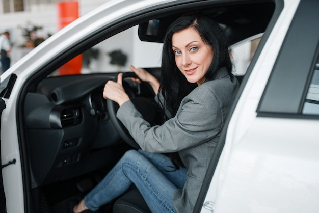 쇼룸에서 새 차를 사는 여자, 바퀴 뒤에 아가씨.