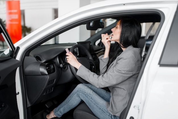 Woman buying new car in showroom, lady paints her lips with lipstick behind the wheel.