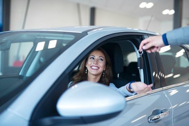ディーラーで新しい車を買う女性。