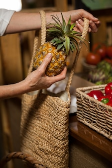 Woman buying pineapple at organic section