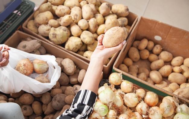 Женщина покупает картофель в продуктовом магазине.