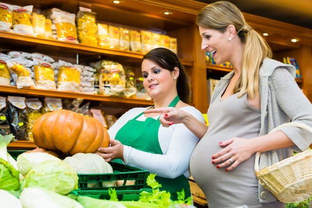 Woman buying pumpkin and vegetables in delicatessen
