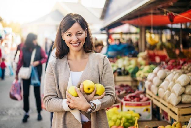 グリーンマーケットの場所で健康的な食生活の女性。