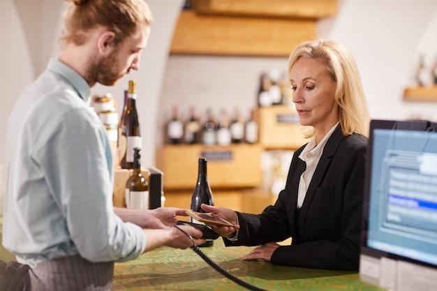 Женщина покупая вино