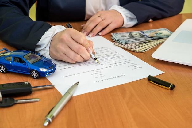 여자는 계약에 서명하는 차를 구입