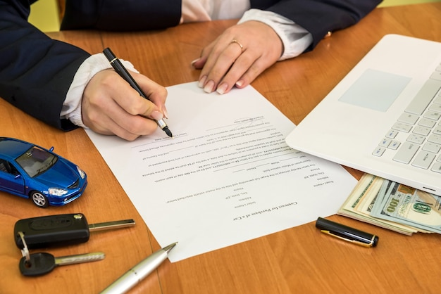 女性が契約に署名する車を購入する