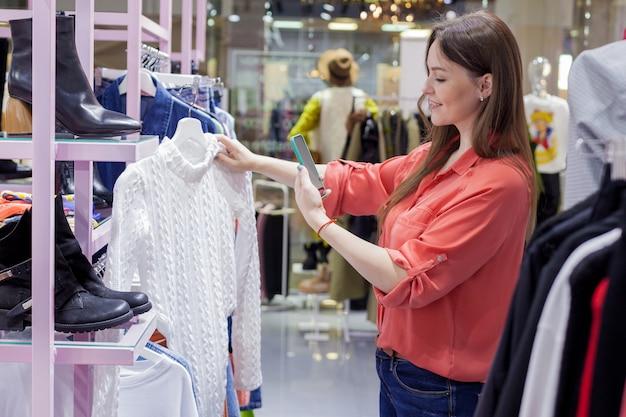 女性は店で白いセーターを買います。