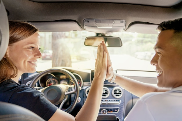 A woman buys a car or takes a car for rent. perhaps an asian boyfriend gave a car, a handshake in the car, laughter and joy.