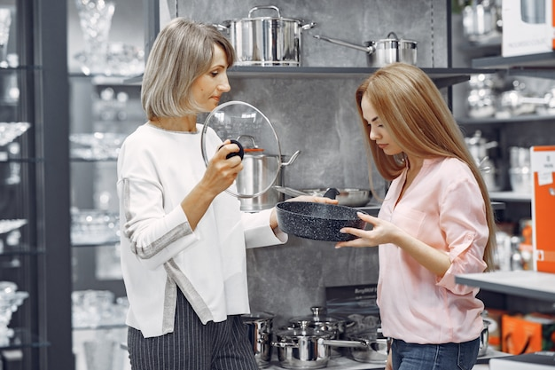 Женщина покупает посуду в магазине