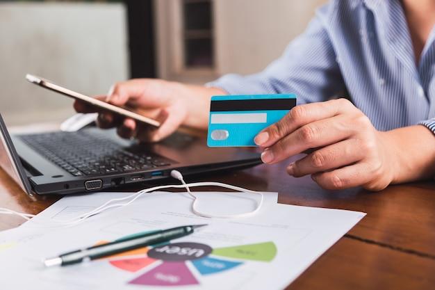 女性はスマートフォンとクレジットカードを使ってオンラインで購入します。 eコマースの概念。
