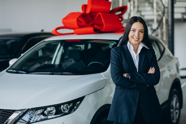 Woman by the car with big red bow