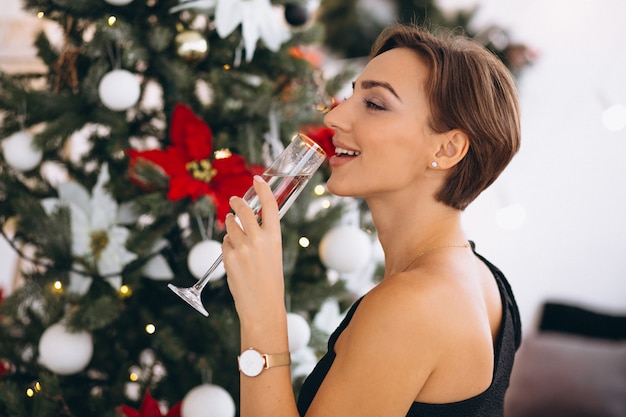Woman by christmas tree drinking champaigne