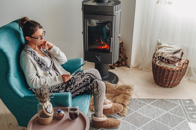 Woman by the fireplace sitting in a cozy armchair with a warm