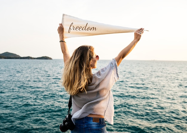 Donna in riva al mare che tiene bandiera con iscrizione di libertà