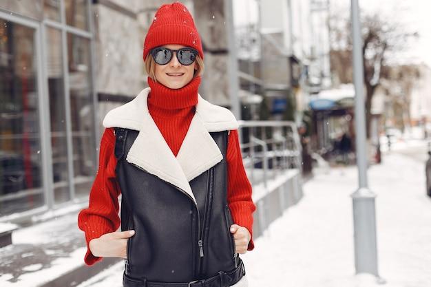 建物のそばの女性。新年の気分。黒のジャケットを着た女性。