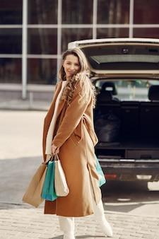 車で買い物袋を持つ女性