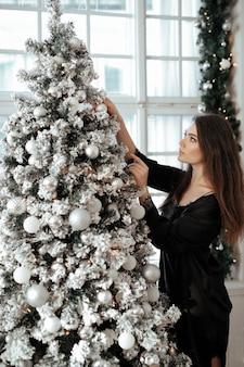 クリスマスツリーのそばの女性