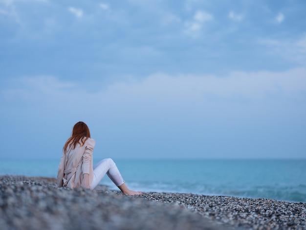 Женщина у океана песчаные камни пляж модель теплые брюки-свитера. фото высокого качества